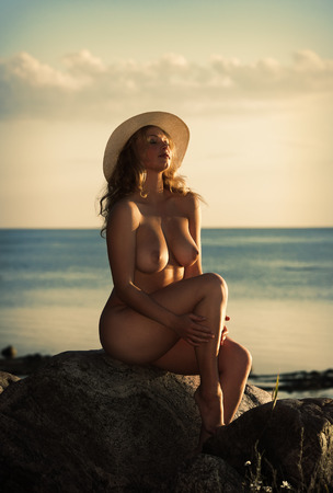 hat nude: Young nude woman with a white hat posing on the beach in the evening sun. Evening light with deep shadows and color shift