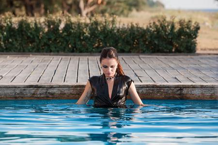 ragazza nuda: Elegante giovane donna bagnata in abito nero in piedi in acqua in una piscina
