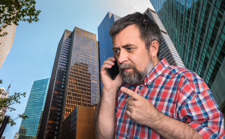 megalopolis: Middle-aged businessman talking on mobile phone in the megalopolis