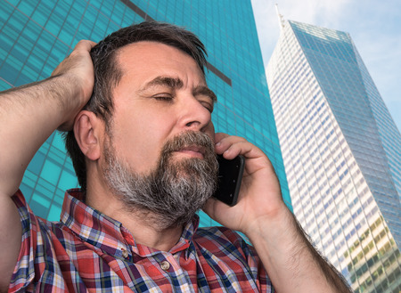 megalopolis: Hard talk. Middle-aged businessman talking on mobile phone in the megalopolis