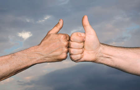 gratified: Friendship concept. Two men bumping fists with thumbs up against sky with clouds Stock Photo