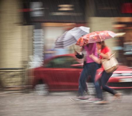 lluvia paraguas: La gente que camina por la calle en día de lluvia. El desenfoque de movimiento intencional