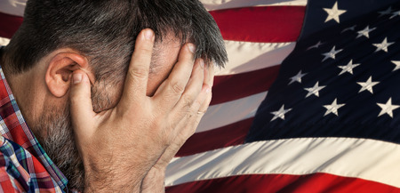 Veteran. Portrait of an elderly man with face closed by hand on USA flag background.