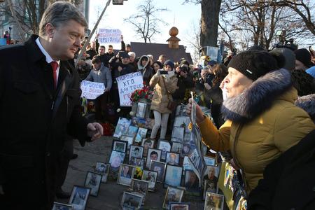dignit�: Kiev, Ukraine - 21 novembre 2014: Pr�sident de l'Ukraine Porochenko entour� parents de h�ros tomb�s centaines de ciel pr�s de la croix comm�morative au lieu d'ex�cution des r�volutionnaires de la dignit� du 20 F�vrier