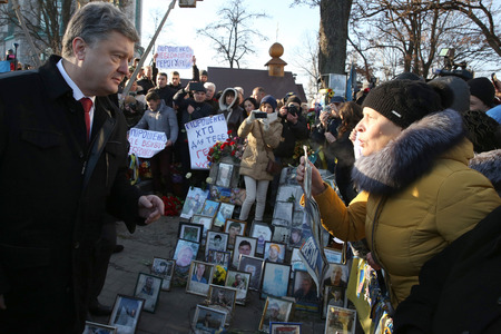 european integration: KIEV, UKRAINE - NOV 21, 2014: President of Ukraine Poroshenko surrounded relatives of fallen heroes Hundreds of Heaven near the memorial cross at the place of execution of the Revolutionaries of Dignity of February 20 Editorial