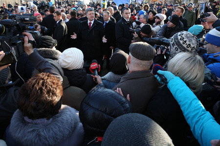 outcry: KIEV, UKRAINE - NOV 21, 2014: President of Ukraine Poroshenko surrounded relatives of fallen heroes Hundreds of Heaven near the memorial cross at the place of execution of the Revolutionaries of Dignity of February 20 Editorial