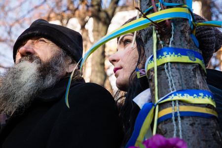 memorial cross: KIEV, Ucraina - NOV 21, 2014: Le persone che pongono fiori vicino la croce commemorativa presso il sito di omicidio dei partecipanti della Rivoluzione della Dignit� del 20 febbraio 2014 Editoriali