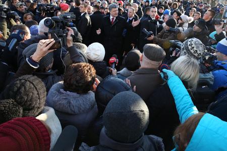 dignidad: KIEV, Ucrania - 21 de noviembre 2014: Presidente de Ucrania Poroshenko rodeado familiares de los h�roes ca�dos Cientos de cielo cerca de la cruz conmemorativa en el lugar de la ejecuci�n de los revolucionarios de la Dignidad de 20 de febrero