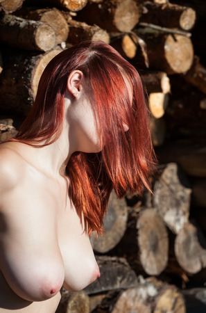 Young nude woman against pile of wooden logs photo
