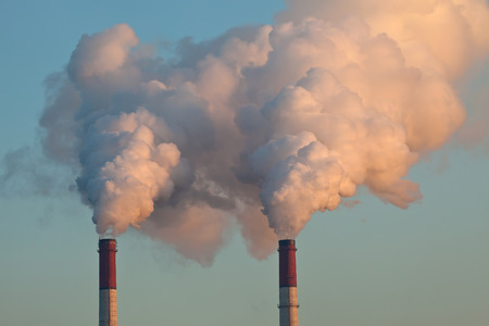 air pollution: Factory pipes throwing out clouds of smoke and polluting the air Stock Photo