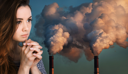 polluting: Ecological concept. Young woman prays against the background of pipes polluting an atmosphere
