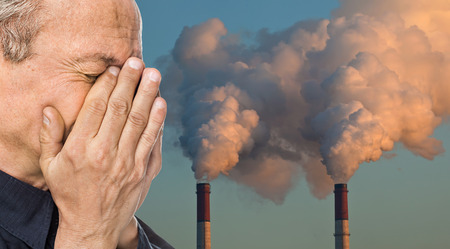 Ecological concept. Elderly man with a face closed by hands against the background of pipes polluting an atmosphere Stockfoto