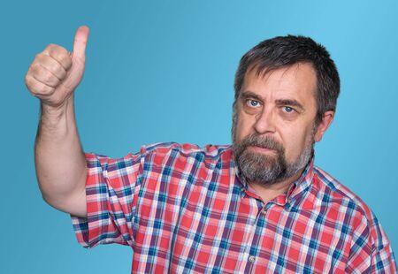 tumb: Middle-aged man tumb up on blue background Stock Photo