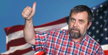 Patriotic concept. Middle-aged man tumb up against of United States of America flag