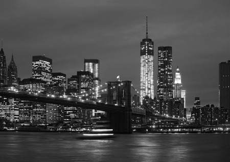 Brooklyn Bridge, East River and Manhattan at night with lights and reflections. New York City Stock Photo