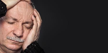 pangs: an older man suffering from a headache on dark background