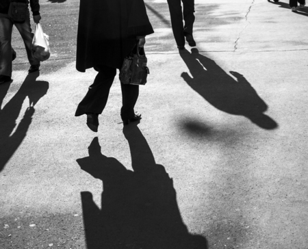 strangers: Shadows of people walking in a street in morning light