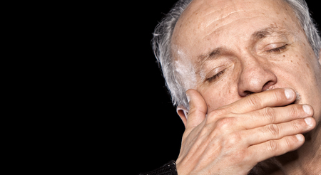 boca cerrada: Un anciano con los ojos cerrados y la boca se cierra aislados en negro con espacio de copia Foto de archivo