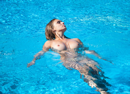wet breast: Beautiful young naked woman in swimming pool