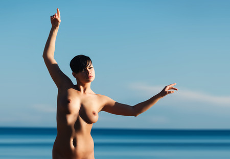 Beautiful naked woman on the beach against the sea and blue sky photo