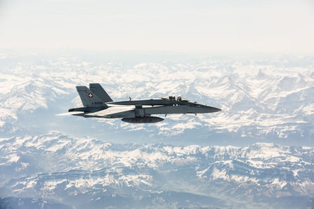 f18: ALPS, SWITZERLAND - Apr 21, 2015: F-18 fighter jet of Swiss military air force on combat duty in the skies over Switzerland in the area of the Swiss Alps