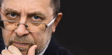 male hands: Portrait of handsome senior man with glasses prop up the head with his hand and copy-space