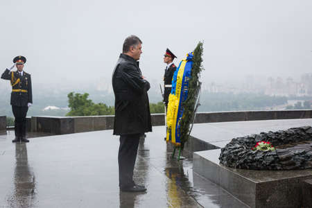 tomb unknown soldier: KIEV, UKRAINE - Jun 22, 2015: President of Ukraine Petro Poroshenko during a wreath-laying ceremony at the Tomb of the Unknown Soldier in the Park of Glory in Kiev