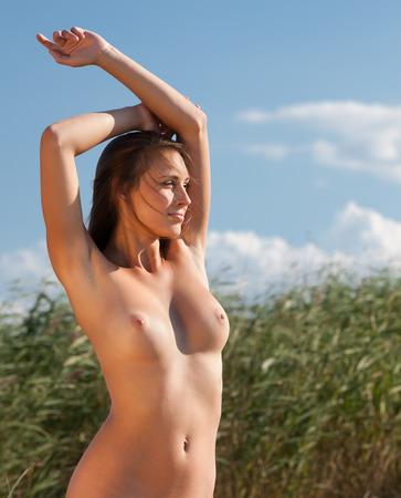 nue plage: Belle jeune femme nue sur la nature de fond Banque d'images