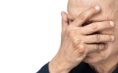 sick person: Pain. Elderly man covers his face with hand isolated on white background with copy-space