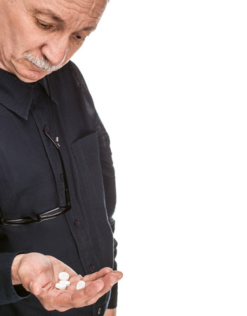 pangs: Old man wants to take a pill isolated on white background with copy-space Stock Photo