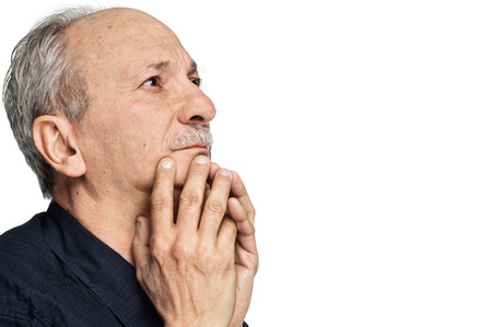 Elderly man with hands near his face looking up isolated on white background with copy-space