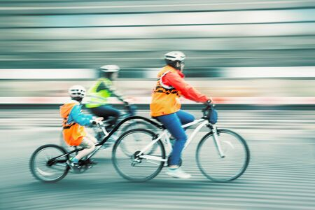 young  family: Young family with a child ride a bikes on a city streets. Intentional motion blur and color shift