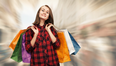 shoping: Sale. Happy young woman with shoping bags on blurred city street background