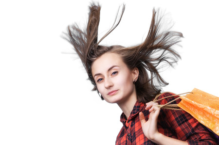 dishevel: Young woman with long blowing hair and shoping bags isolated on white background with copy-space