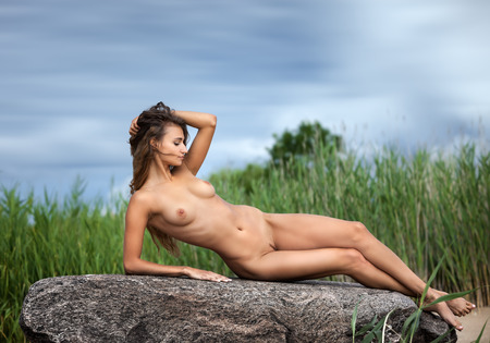 bare breast: Beautiful young nude woman on nature background Stock Photo