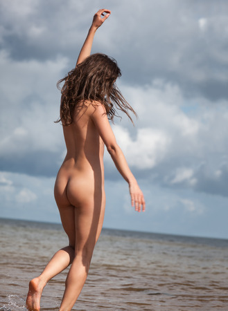 nude outdoors: Beauty girl outdoors enjoying nature. Young naked woman on the beach Stock Photo