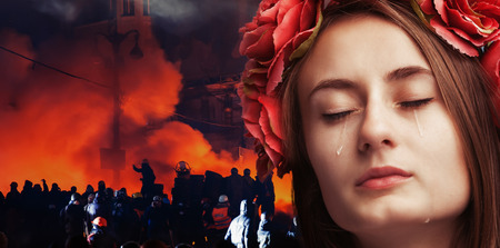 outcry: Patriotic concept Ukraine in fire. Close-up portrait of beautiful crying girl with tears on her cheeks against the background of mass riots