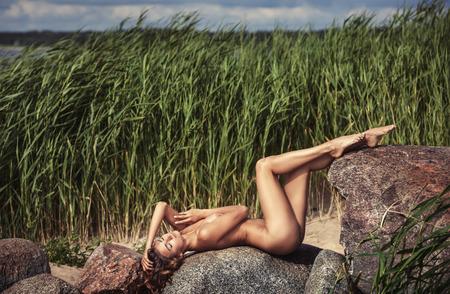desnudo de mujer: Beautiful young nude woman on nature background Foto de archivo