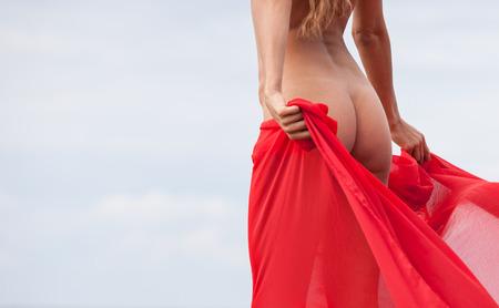 desnudo de mujer: Hermosa mujer desnuda con la presentaci�n de la tela roja en la playa del mar contra el cielo