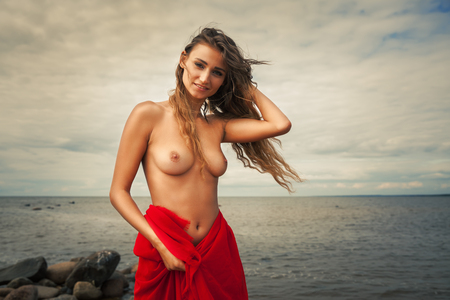 beach breast: Beautiful nude woman with red fabric posing on sea beach against sky background