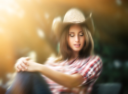 sexy glamour: Blurred portrait of sexy cowgirl in sun light. Young woman in a hat
