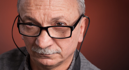 Close up portrait of an elderly man with glasses woth copy-space