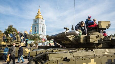 considering: KIEV, UKRAINE - Oct 17, 2015: Exhibition of military equipment Power of Unbroken on the occasion of the Day of Defender of Ukrain. Children are considering military equipment