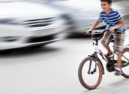 bicicleta: Situación peligrosa tráfico de la ciudad con un muchacho en la bicicleta y los coches en movimiento borroso. desenfoque de movimiento intencional Foto de archivo