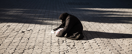 social outcast: Poor woman on the street begging for money
