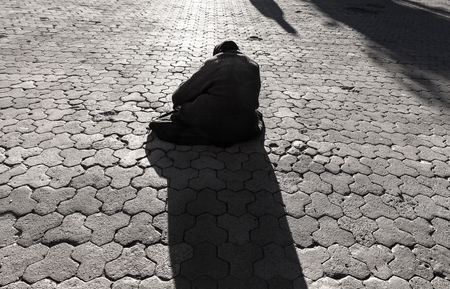 vagabond: Silhouette of beggar old woman sitting on the street and begging for money