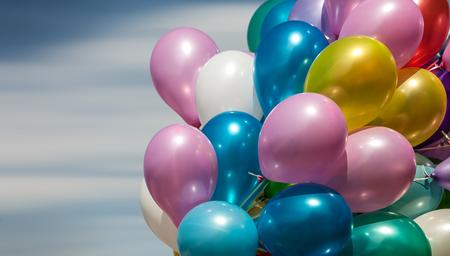 marco cumpleaños: Manojo de globos de colores sobre un fondo de cielo azul