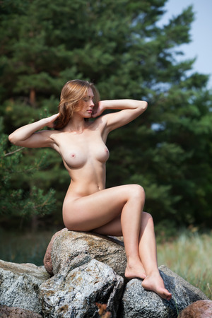 nude nature: Beautiful nude woman sitting on stones against nature background