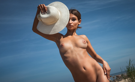nudity young: Young elegant nude woman with a white hat posing on the beach against blue sky with copyspace Stock Photo