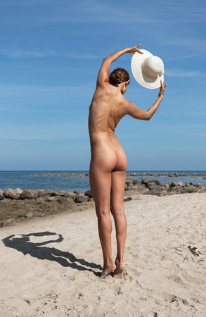 nude nature: Young elegant nude woman with a white hat posing on the beach